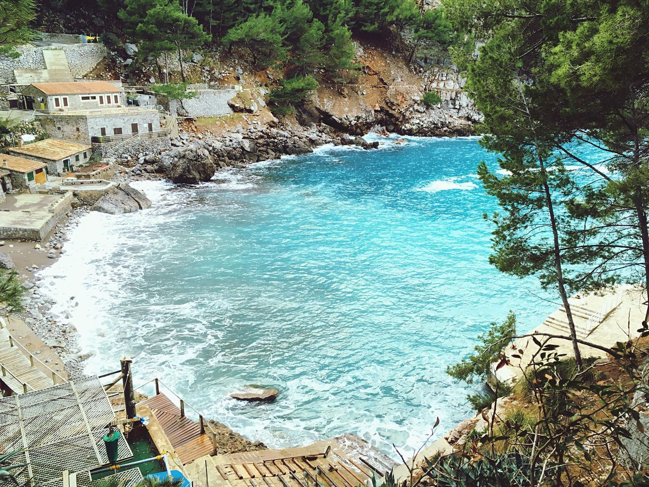 water, high angle view, built structure, architecture, day, nature, sea, building exterior, tree, plant, land, outdoors, beauty in nature, scenics - nature, incidental people, rock, beach, solid, turquoise colored