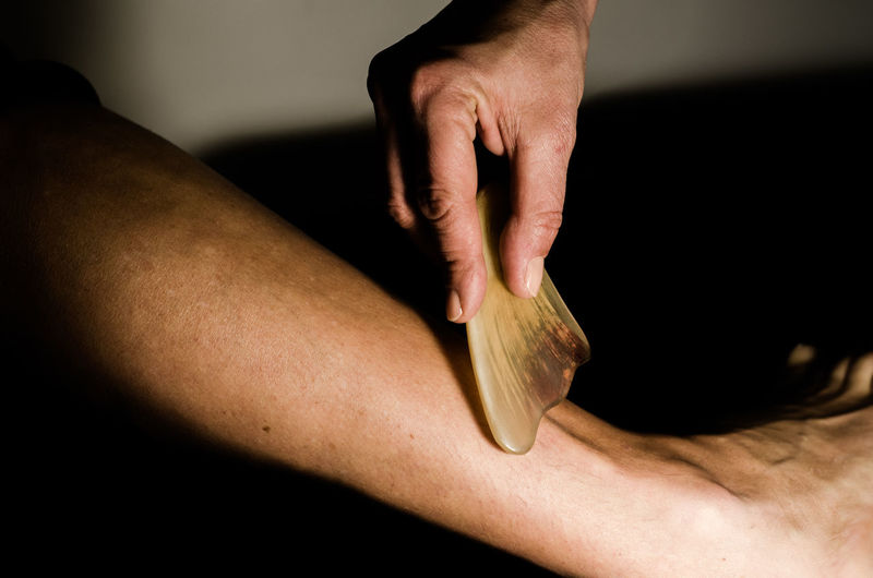 Cropped Hand Of Massage Therapist Massaging Human Leg