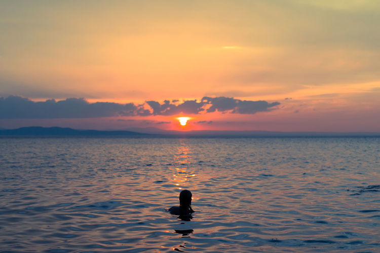 Silhouette person swimming in sea at sunset