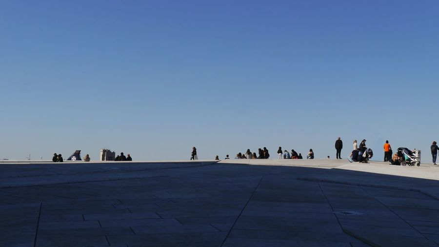 large group of people on roof top Large Group Of People Rooftop Low Angle View Blue Sky Light And Shadow Architecture Resting On Roof Top Opera House Oslo, Norway people and places EyeEm Gallery The Purist (no Edit, No Filter) Taking Photos Travel City Sky The Traveler - 2019 EyeEm Awards
