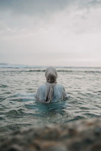 Rear view of woman in hijab enjoying in sea at beach against sky
