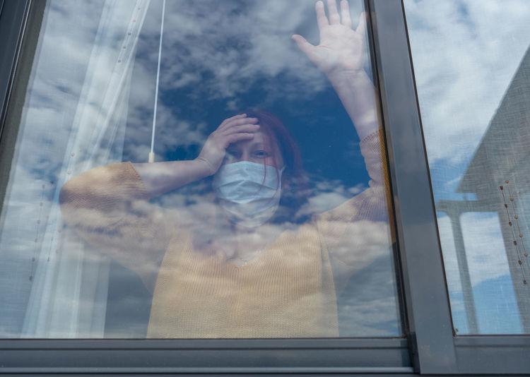 Portrait of woman seen through glass window