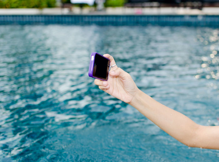 Cropped Hand Of Woman Taking Selfie In Swimming Pool