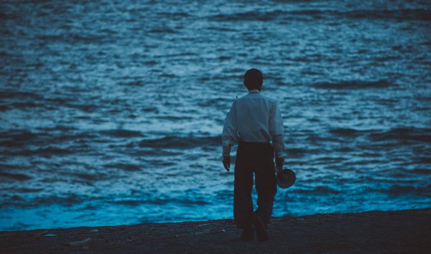 Rear view of man walking towards sea during sunset