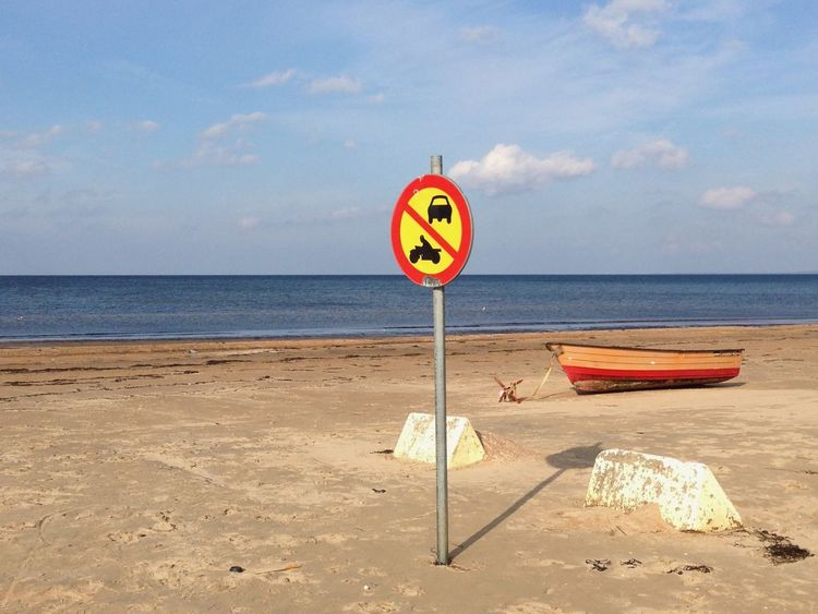 Trafic sign on a beach. A boat has ancored on the beach. Colors EyeEmNewHere Fun Funny Laholm Laholmsbukten Nature Scenic Trafic Signs Beach Colorful Day Mellbystrand Mysterious Mystery No People Outdoors Professionalphotography Sand Sea Sea And Sky Shore Trafic Sign Water Where Am I?