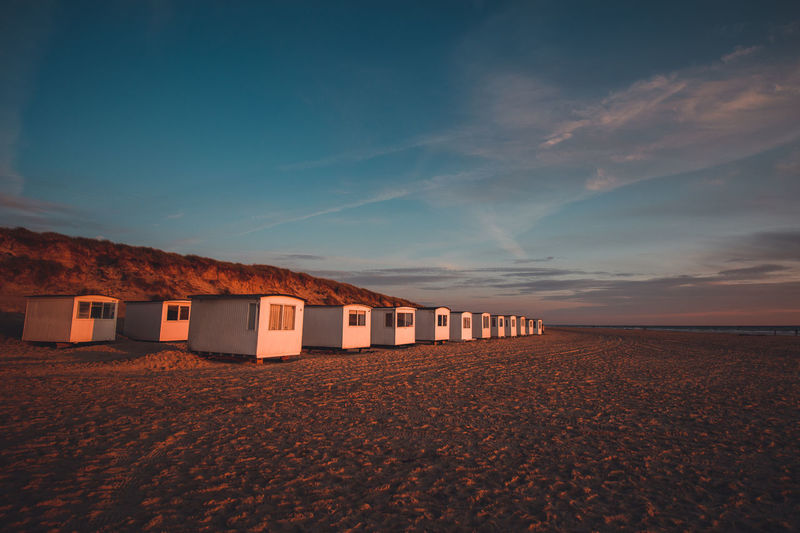 Huts at beach against blue sky during sunset