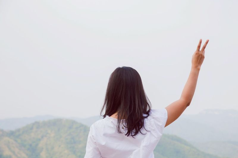 Rear view of woman standing in mountain against sky