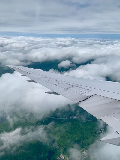 Aerial view of aircraft wing against cloudy sky