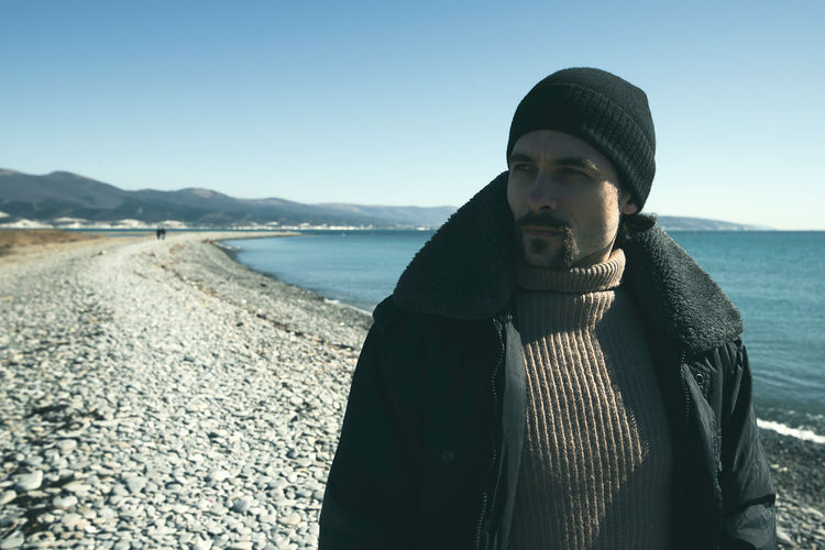 A young man walks on the beach. Seacoast in the background. One person in the frame. Man on the background of a clear sky. He is warmly dressed in boots, jeans, a sweater, a jacket and a hat. Casual wear. The guy wears a mustache and stubble. Hair out of the caps. Winter sunny day. Live photo. Lifestyles Lifestyle Authentic Moments Authentic Candid Real People Life People People Watching people and places Sea Water Beach Warm Clothing Daylight Day Looking Away Life In Motion Males  Man One Person Mid Adult Facial Hair Hat Portrait
