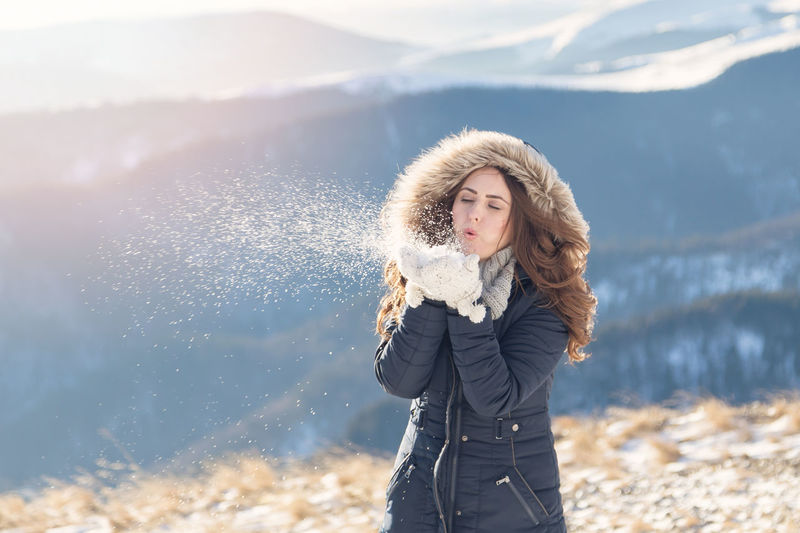 Winter portrait of a beautiful woman in the snowfall Portrait Of A Woman Beauty In Nature Closeup Cold Temperature Day Gloves Leisure Activity Mountain Mountain Range Nature One Person Snow Snowfall Warm Clothing Winter