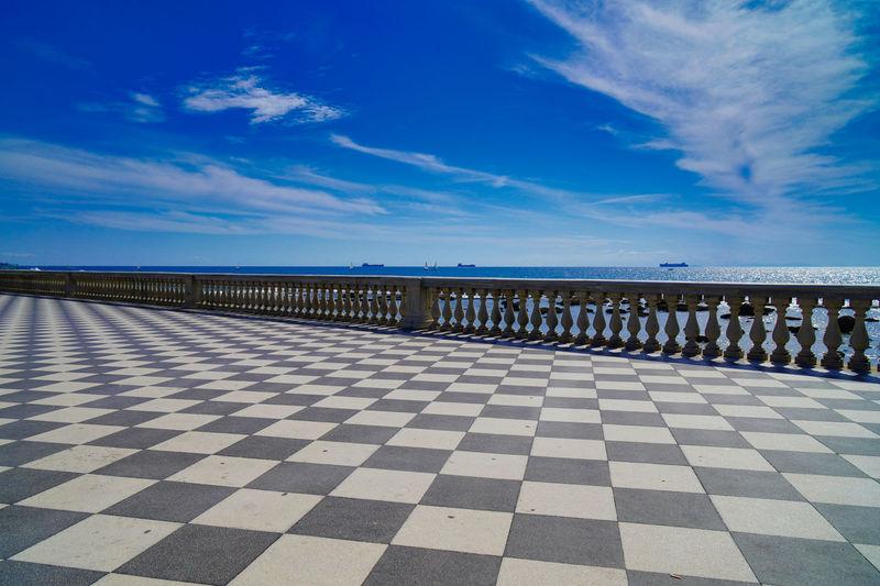 Scenic view of boulevard at sea against blue sky