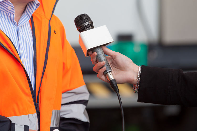 Cropped image of reporter taking interview of man