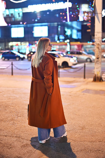Rear view of woman standing on street at night