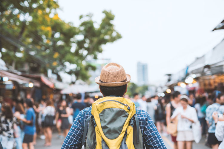 Man wearing hat while standing at market in city