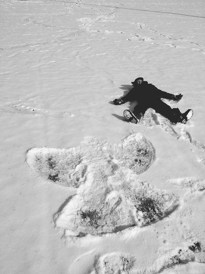 High Angle View Of Child Making Angel On Snowfield