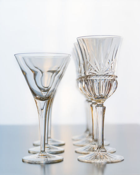 Decoration setup of wine and martini glasses set on a reflective table top. Glass Glass - Material Drinking Glass Transparent Still Life Close-up Drink Food And Drink Table Indoors  Studio Shot No People Wineglass Refreshment White Background Empty Reflection Luxury Martini Glass Details Rows Reflection Shiny Bright Elegence