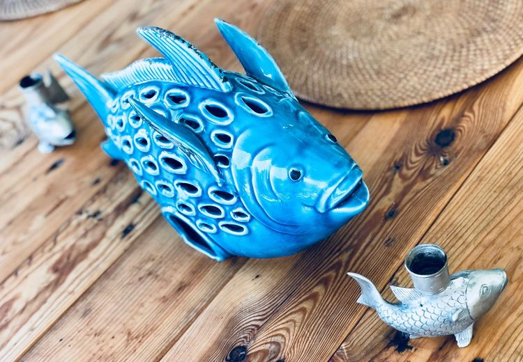 High angle view of fish figurines on wooden table