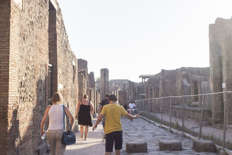 Rear view of people walking on cobblestone against clear sky