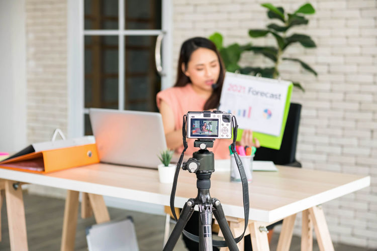 Portrait of woman photographing with camera on table