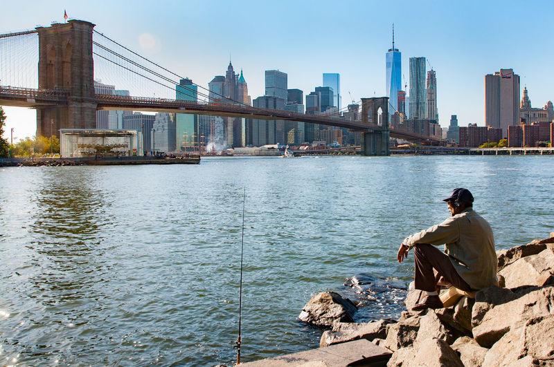 Man sitting brooklyn bridge against sky in city on sunny day