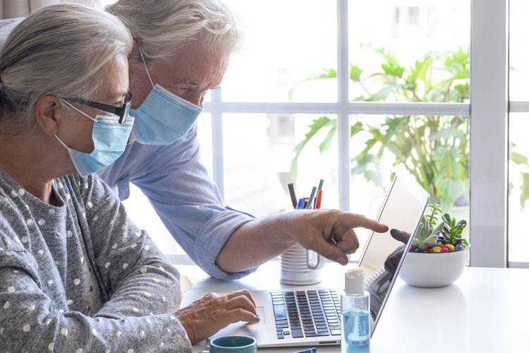 Senior couple wearing flu mask using laptop at home