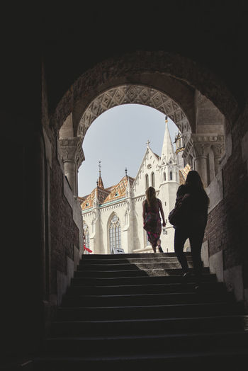 Young women tourists walking towards the church of Matthias from an original point of view in the buda fishermen bastion, budapest Adult Arch Architecture Belief Building Building Exterior Built Structure Day Group Of People History Lifestyles Outdoors Place Of Worship Real People Rear View Religion Spirituality Staircase Steps And Staircases Women