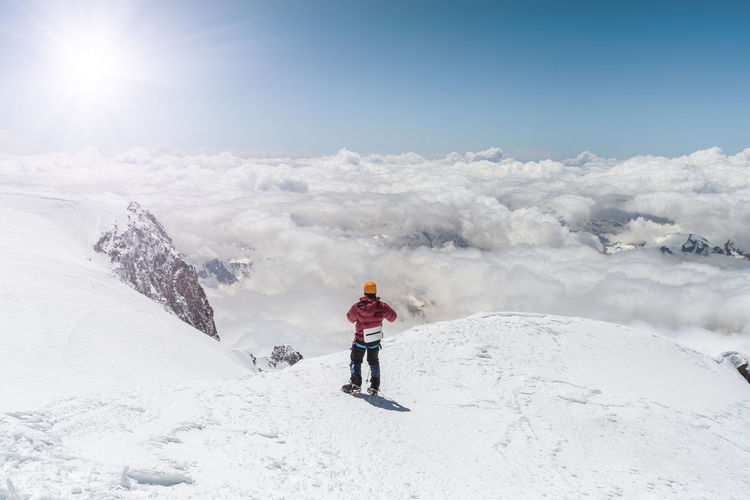 Man standing on snow covered mountain against sky