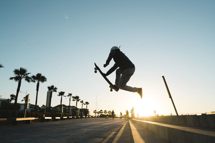 Man jumping on road against clear sky