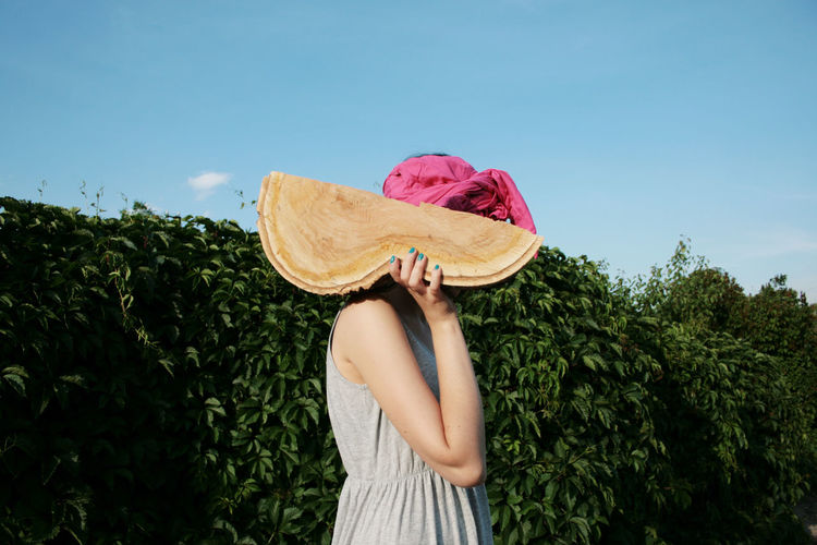 One Person Women Real People Leisure Activity Obscured Face Lifestyles Unrecognizable Person Outdoors Holding Clothing Nature Hedge Summer Hiding Log Wood Girl Young Adult Young Women Girls Greenery Green Color Weird Strange Odd