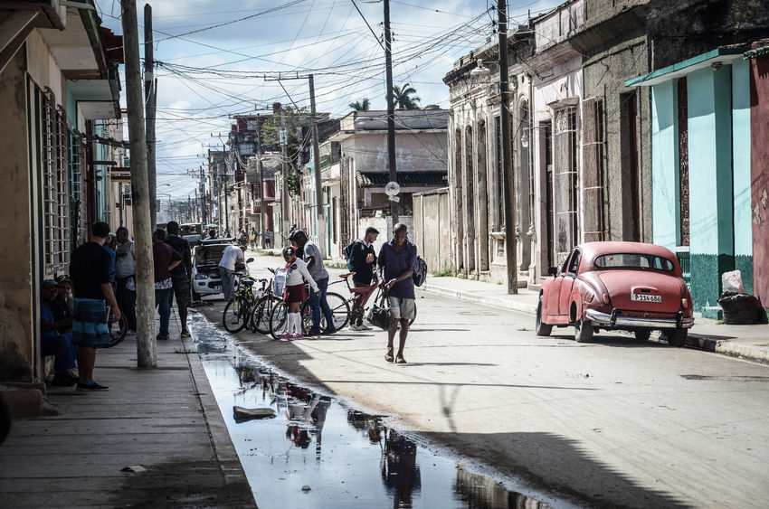 Adult Architecture Building Exterior Built Structure Cable City Day Electricity Pylon Land Vehicle Large Group Of People Life On Street Men Mode Of Transport Outdoors People Real People Road Sky Transportation Women