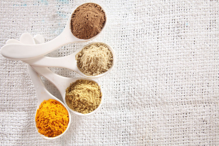white spoon with curve fill up with ground spices Spice In A Row Arrangement Condiment Seasoning Assortment Variety Variation High Angle View Directly Above Ingredient Food Food And Drink Ground - Culinary Chili Pepper Red Hot Spicy Turmeric  Cinnamon Pepper Coriander Cumin Cardamom Still Life