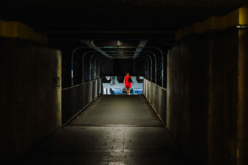 Rear View Of Woman Walking In Illuminated Underground Walkway