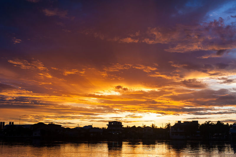 Silhouette city by river against romantic sky at sunset