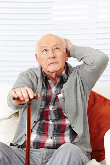 Thoughtful senior man sitting on couch at home