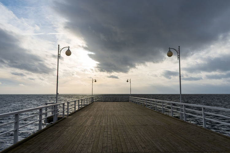 Street lights on footpath by sea against sky