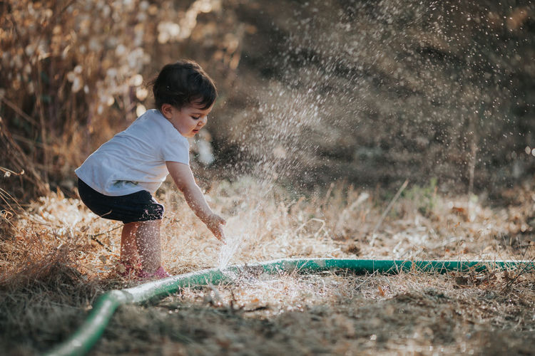 Baby girl standing by water spraying from hose on land
