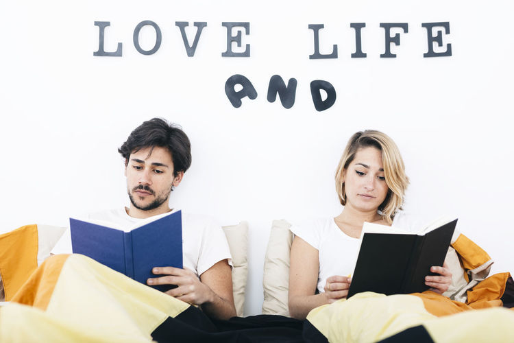 Young couple reading books in bed. Bed Couple In Bed Love Man Reading Relationship Woman Adult Bedroom Book Day Indoors  Lifestyles Men People Relax Relaxation Sitting Text Two People Young Adult Young Men Young Women
