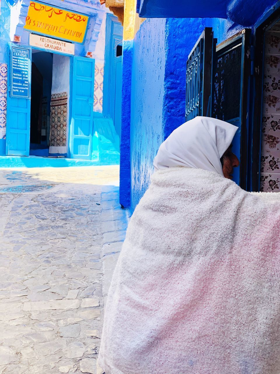 architecture, built structure, building exterior, building, day, real people, blue, door, entrance, sunlight, people, rear view, clothing, outdoors, textile, house, window, city