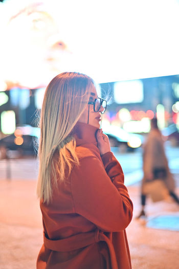 Midsection of woman wearing sunglasses standing in city