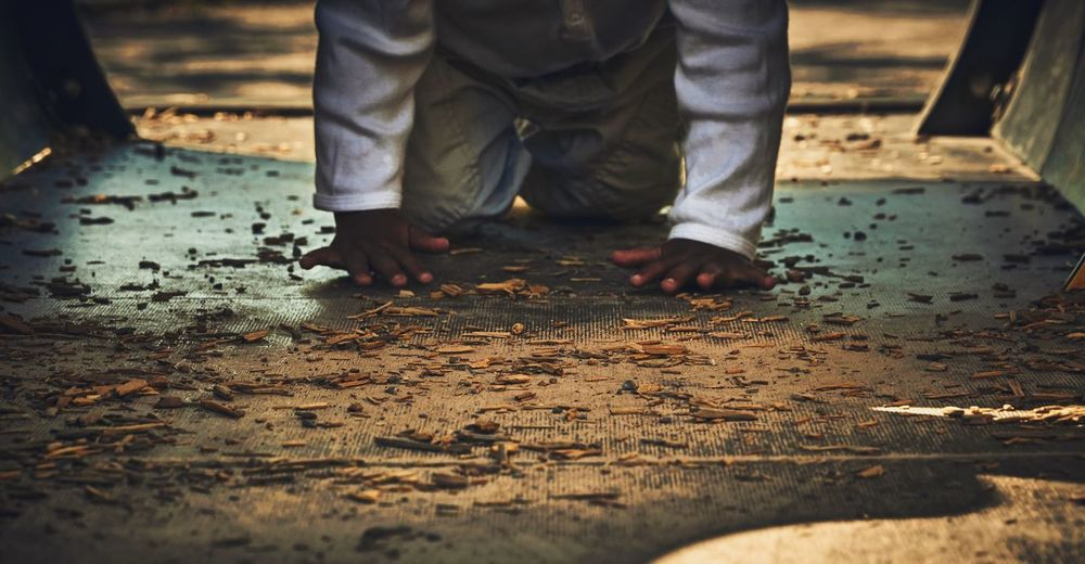 Midsection of boy crawling on footpath