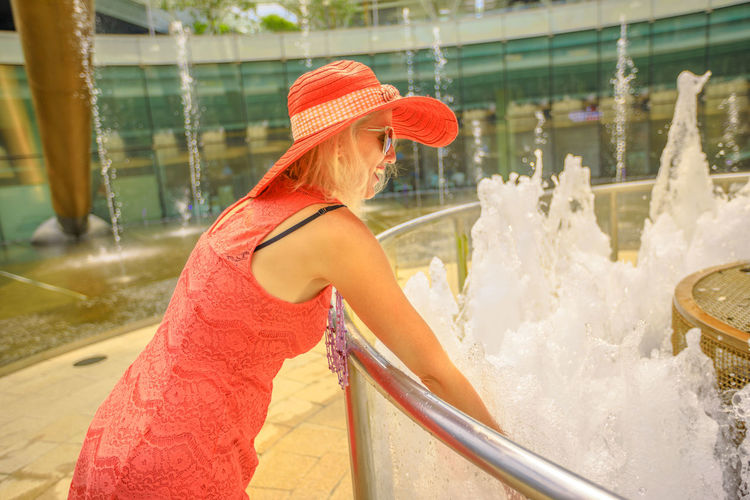 Happy tourist enjoying at largest fountain in the world. Fountain of Wealth at Suntec Tower the biggest fountain in Singapore. Lifestyle woman with wide hat touch water of fountain to get luck. Singapore Singapore City Woman Tourist Tourist Attraction  Tourist Destination People Girl Females Happy Travel Hat Lifestyle Enjoy Nature Tourism Smiling Fountain Of Wealth Fountain Wealth Management Luck Lucky Water One Person Women Adult Waist Up Day Hair Motion Clothing Leisure Activity Young Adult Focus On Foreground Hairstyle Enjoyment Happiness Fun Beautiful Woman Outdoors