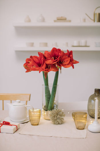 Close-up of red rose in vase on table at home