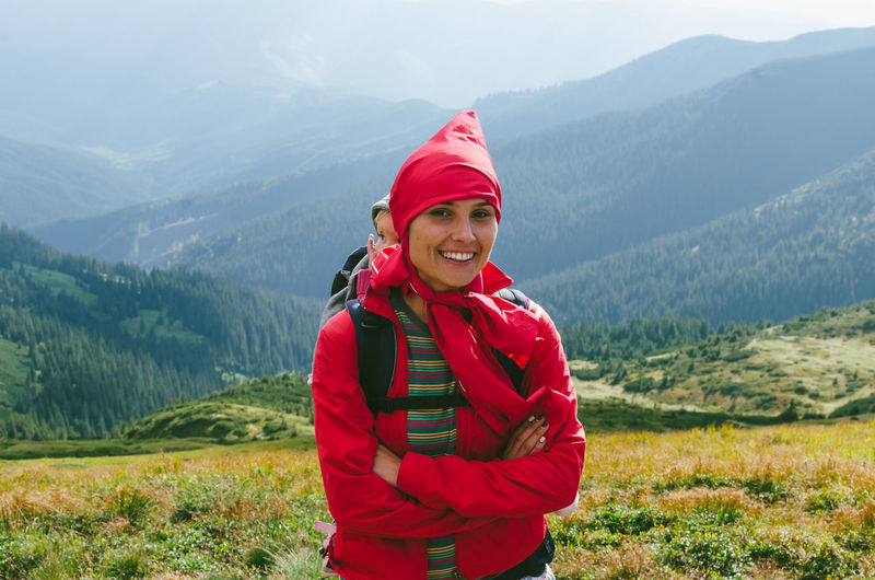 Portrait Of Smiling Mother Carrying Daughter While Standing On Mountain