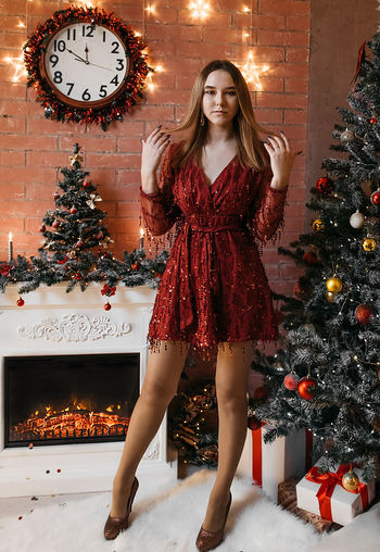 Full length portrait of woman standing in illuminated christmas tree