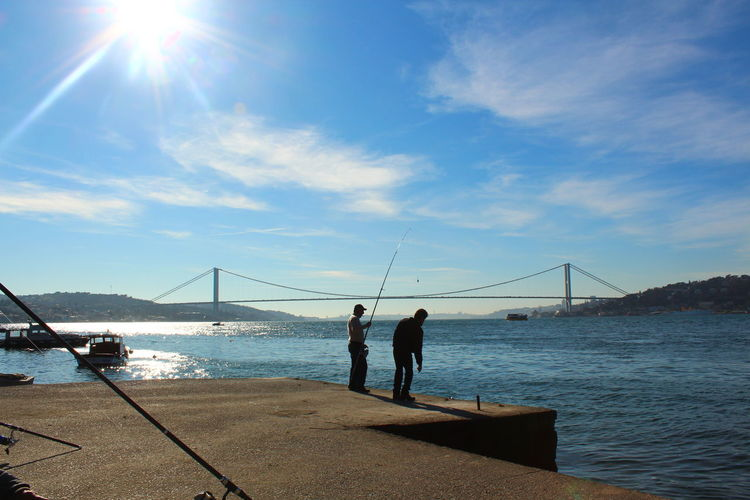 Men fishing at harbor with bosphorus bridge in background against sky