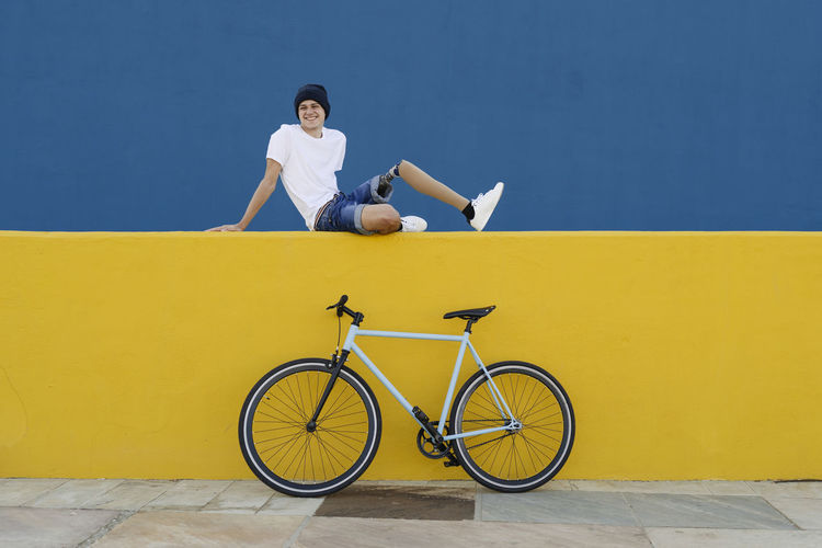 Woman sitting on bicycle against yellow wall