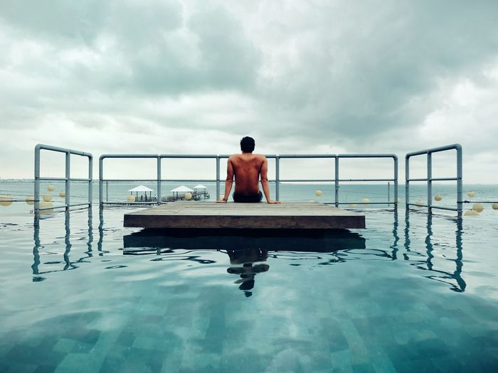Shirtless man sitting on floating platform in swimming pool against sky