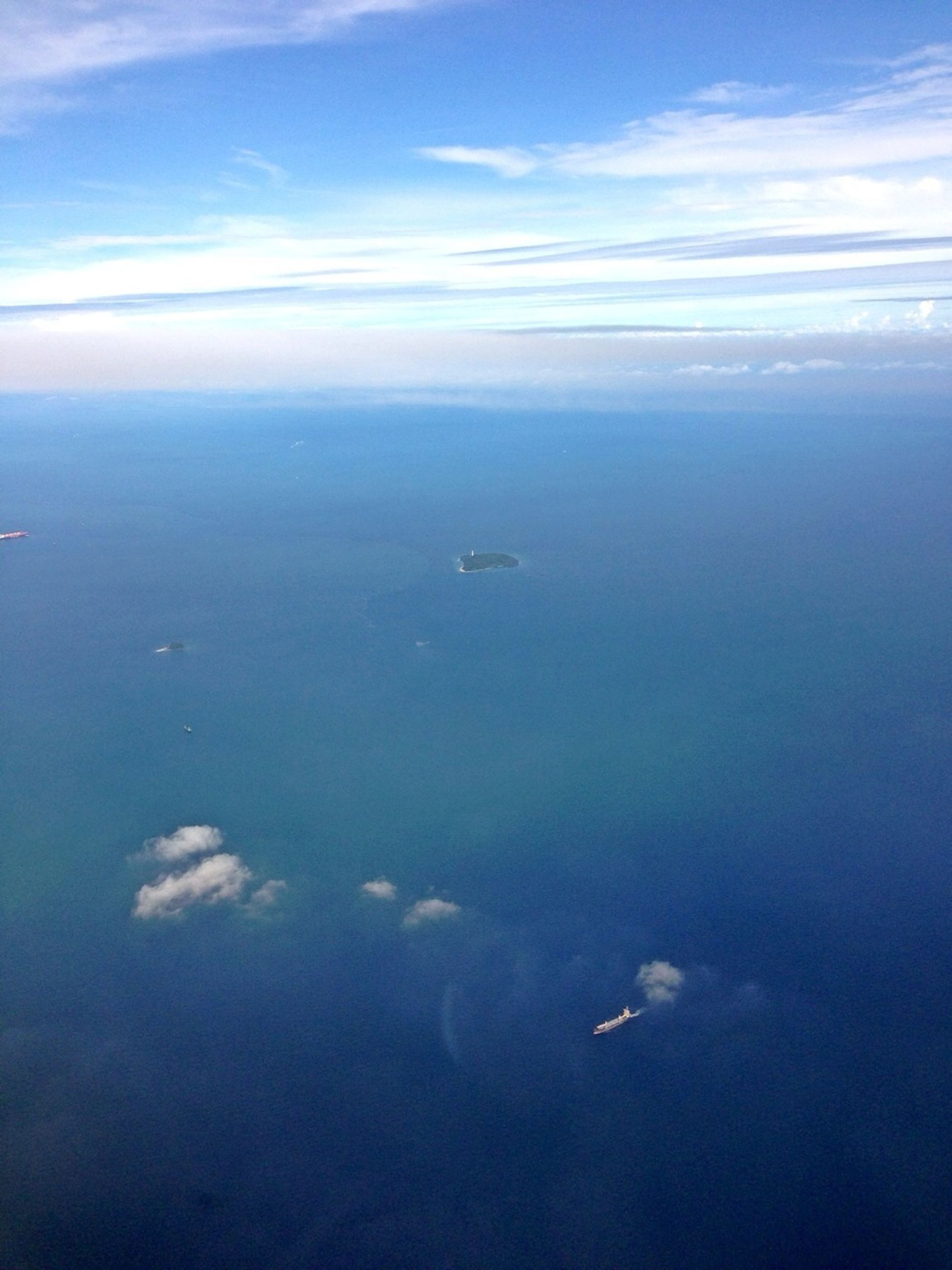 sea, water, scenics, flying, tranquil scene, blue, beauty in nature, sky, aerial view, tranquility, transportation, nature, mode of transport, horizon over water, waterfront, cloud - sky, idyllic, airplane, seascape, travel