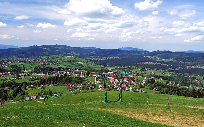 Koniakow village with hills on the background from Ochodzita hill in Beskid Slaski mountains in Poland Beskid Slaski Poland Architecture Blue Sky With Clouds Cloud - Sky Countryside Grass Hill Koniaków Landscape Mountain Mountain Range Nature Ochodzita Outdoors Rural Scene Scenics Sky Village