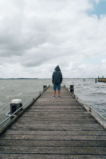 Rear View Of Teenager On Jetty At Sea Against Sky